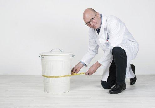 Le professeur Nodéchais prend le tour de taille de la poubelle
